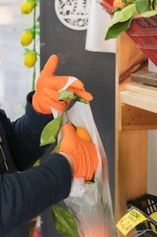 Avetrana, italië, - marth 16, 2020. een italiaanse groenteman doet oranje in een zak, draagt een medisch masker en draagt handschoenen die de gezondheidsnormen respecteren tijdens de epidemie van het coronavirus.