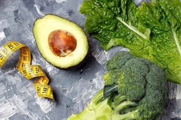 Avocado, broccoli en meetlint op grijs, dieet