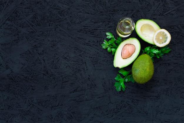 Avocado, citroenpeterselie, plantaardige olie, olijfolie, avocado-olie op een zwarte achtergrond.