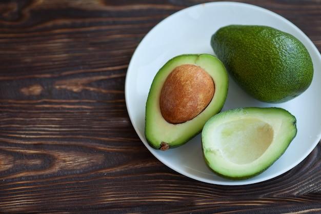 Avocado en avocado stukken op een houten vloer en heeft een achtergrond van de natuur geselecteerde focus