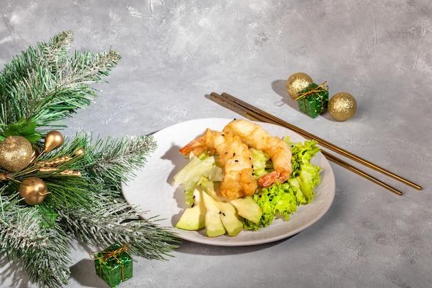 Avocado en gambasalade op groene bladeren. feestelijk diner. gezond eten. op een roze achtergrond. kopieer ruimte.