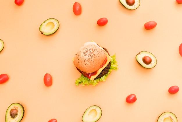 Avocado en kersentomaten die rond de hamburger op gekleurde achtergrond worden omringd
