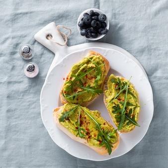 Avocado en rucola sandwich met paprika op de tafel. gezond ontbijt of snack op een bord op een blauw linnen tafellaken