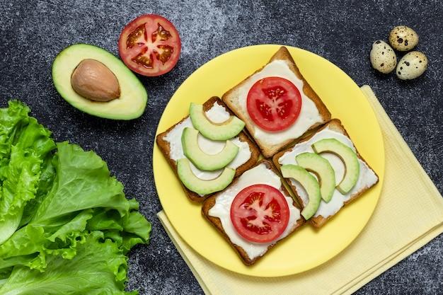 Avocado- en tomatensandwiches op een gele plaat