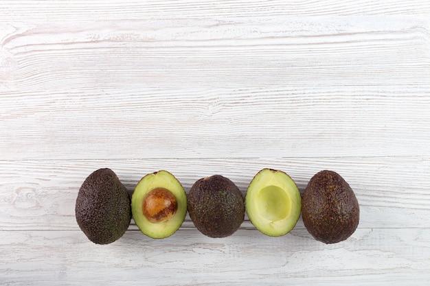 Avocado - gehalveerde en hele avocado's op witte houten achtergrond