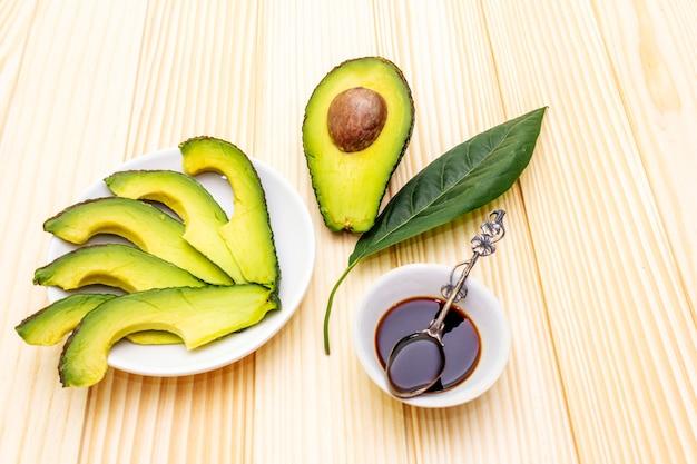 Avocado, in tweeën gesneden met bot, avocadoplakken en avocadoblad met sojasaus