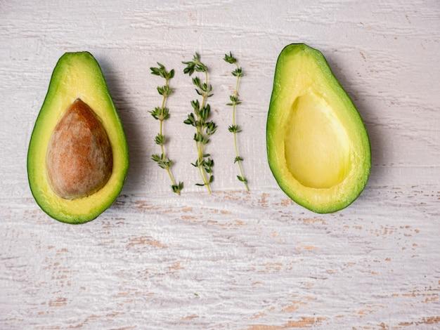 Avocado in tweeën gesneden op een wit houten bord.