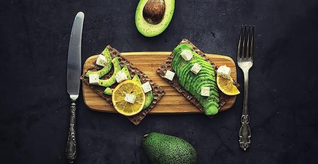 Avocado kookrecepten. rijpe groene avocado op een houten snijplank om te serveren.