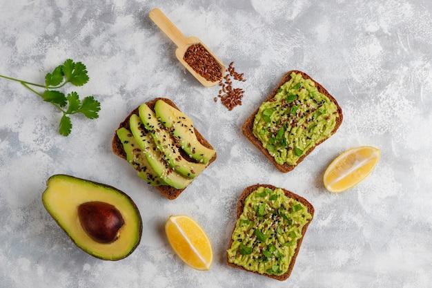 Avocado open toast met plakjes avocado, citroen, lijnzaad, sesamzaadjes, plakjes zwart brood, bovenaanzicht