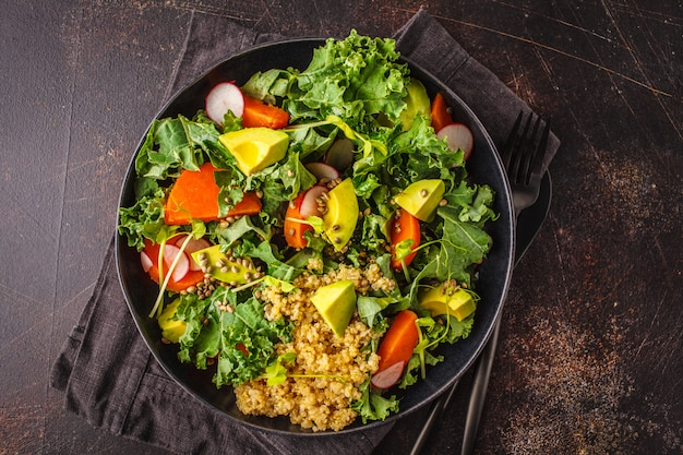 Avocado, quinoa, yam en boerenkoolsalade in zwarte plaat op een donkere achtergrond.