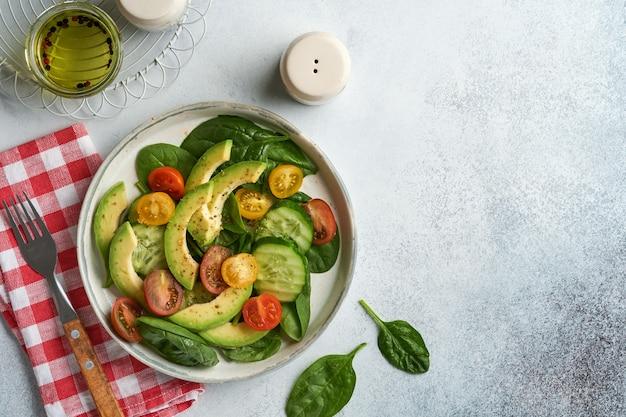 Avocado, rode, gele, zwarte cherrytomaat, spinazie en komkommer verse salade met kruiden, peper en olijfolie in grijze kom op grijze leisteen, steen of betonnen ondergrond. gezond voedselconcept. bovenaanzicht.