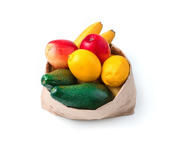 Avocado's, citroenen, bananen en appels in een papieren zak geïsoleerd op een witte achtergrond. het concept van vers fruit.