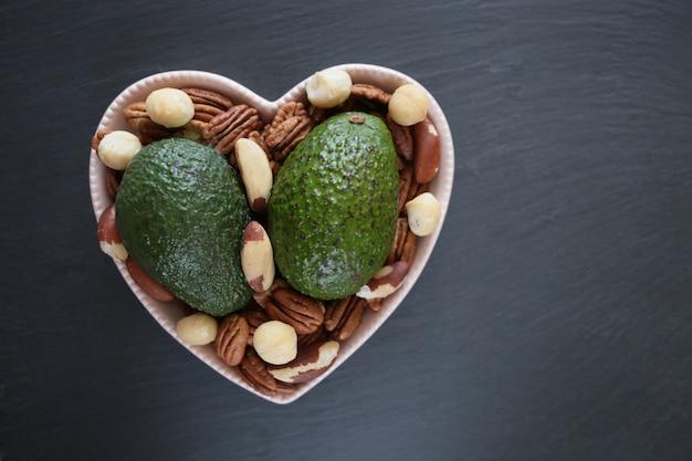 Avocado's en noten. twee rijpe avocado's, pecannoten, paranoten en macadamia noten in een hartvormige schotel