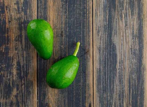 Avocado's op een houten tafel. plat lag.
