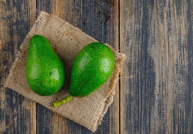 Avocado's op houten en stuk zak. plat lag.