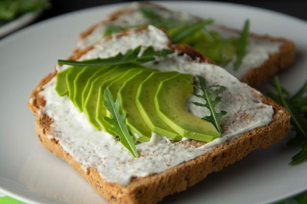 Avocado sandwich toast brood gemaakt met vers gesneden avocado, roomkaas.