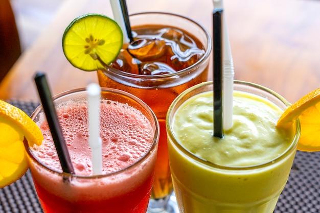 Avocado smoothie, watermeloen shake en koude thee in een glas op een houten tafel. tropisch drankje concept. bovenaanzicht, close-up