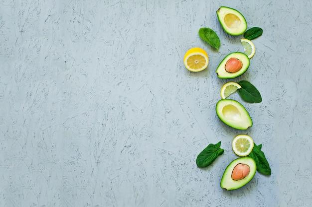 Avocado, spinazie, plantaardige olie, olijfolie, avocado-olie op een grijze achtergrond.