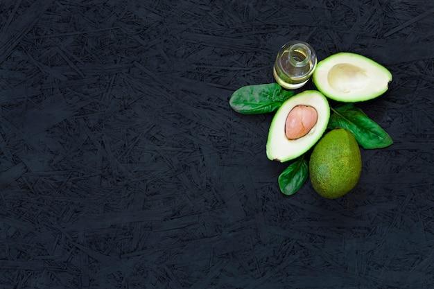 Avocado, spinazie, plantaardige olie, olijfolie, avocado-olie op een zwarte achtergrond.