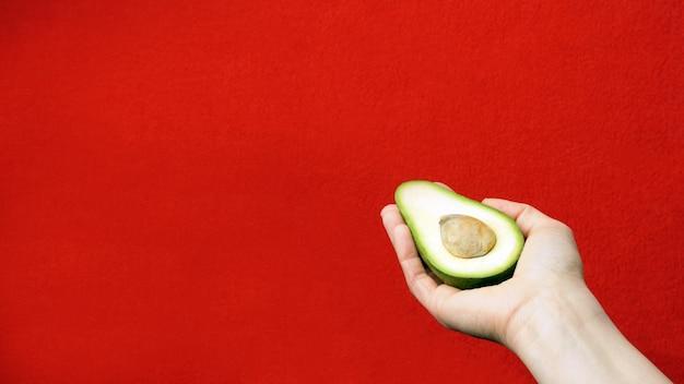 Avocado ter beschikking, met exemplaarruimte. een plakje avocado met een bot in de palm van je hand.