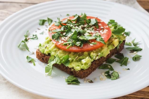 Avocado toast. gezonde toast met avocado puree en tomaten op een plaat.