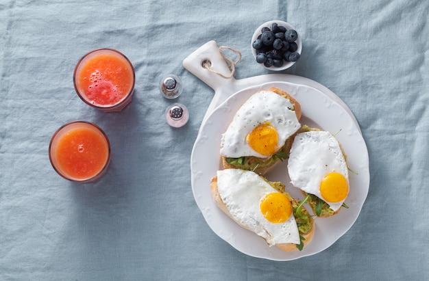 Avocadosandwich en gebakken ei met paprika op de lijst. gezond ontbijt of snack op een bord op een blauw linnen tafellaken en vers geperst grapefruitsap