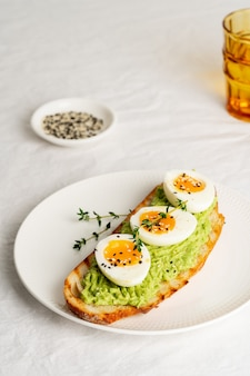 Avocadotoost met geroosterd brood, zachtgekookte eieren met kruiden
