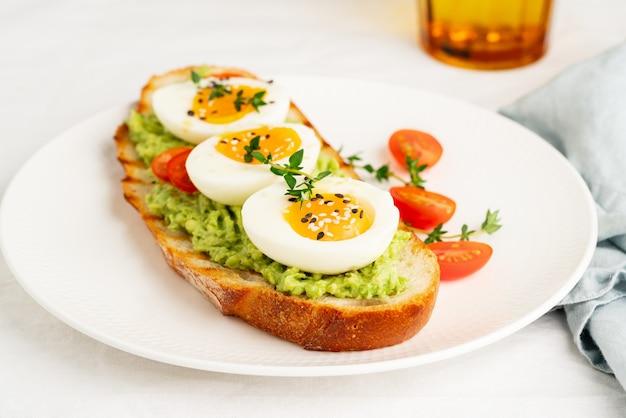 Avocadotoost met geroosterd brood, zachtgekookte eieren met tomaten