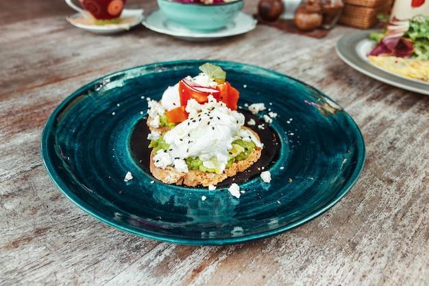 Avocadotoost met roerei op de mooie blauwe plaat op de houten tafelachtergrond