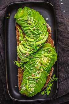 Avocadotoost met roggebrood en zaden op zwarte plaat, donkere achtergrond, hoogste mening.
