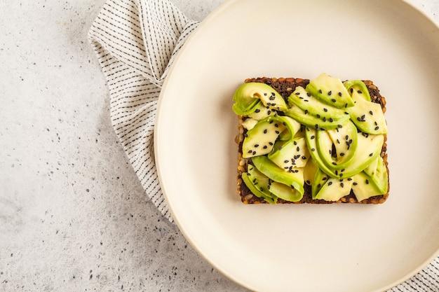 Avocadotoost op een gezond sesambrood met sesamzaden, hoogste mening. gezond veganistisch eten concept.