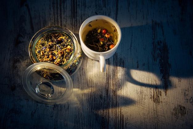 Avond blended thee gemaakt van kruiden, bloemen, bessen en pijnboompitten in het diffuse licht. thee in mok en glazen kom, schaduwen op grijze houten tafel. kruidengeneeskunde, gezondheidsverbetering, gewichtsverlies.