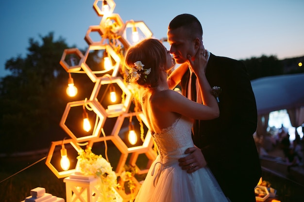 Avond huwelijksceremonie. de bruid en bruidegom staan op de achtergrond van de huwelijksboog.