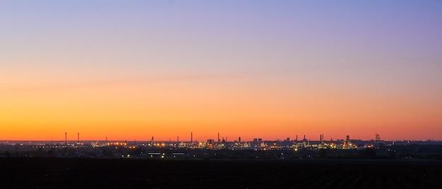 Avond industrieel landschapssilhouet van een olieraffinaderij met aangestoken lichten aan de horizon