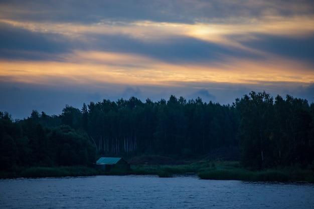 Avond rivierlandschap kalm water en dramatische lucht met wolken ruimte kopiëren