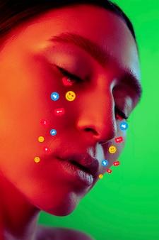 Avond. tranen geïllustreerd van sociale media-activiteitsborden op vrouwelijk gezicht in neonlicht. het echte leven versus online levensstijl, verslaving aan modern technologieënconcept. copyspace voor advertentie. creatief kunstwerk.