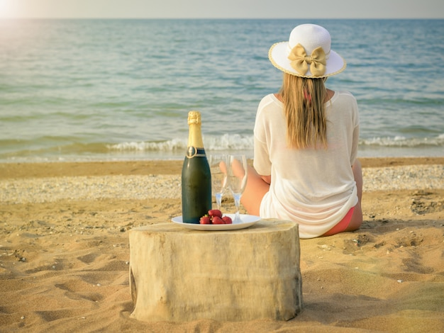 Avond zee landschap met een vrouw met champagne en aardbeien.
