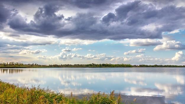 Avond zomer landschap met weelderige pijnboom aan de oevers van de rivier