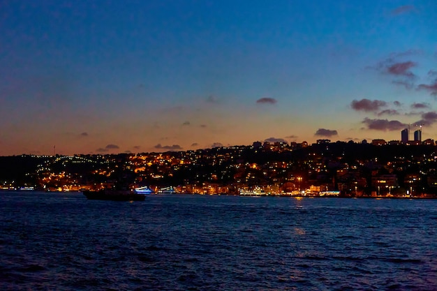 Avondboottocht op de bosporus in istanbul. uitzicht vanaf een boot naar de kust van turkije.