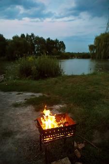Avondbrandend brandhout in de grill, voorbereiding voor het frituren van vlees, nabij het meer
