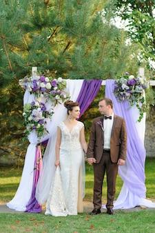 Avondfotosessie van het bruidspaar bij de huwelijksboog na de ceremonie