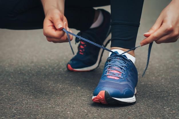 Avondloop. jonge dame die op een landelijke weg tijdens zonsondergang in blauwe sneakers