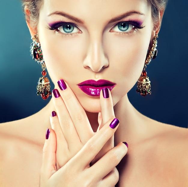 Avondmake-up, met de paarse oogschaduw en felviolette lippenstift. grote oorbellen in haar oren. sieraden cosmetica en manicure