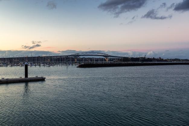 Avondmening van de brug van auckland en kalm water van de haven