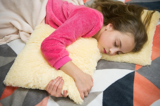 Avondontspanning voor het slapengaan. kinderopvangconcept. aangename tijd ontspanning. geestelijke gezondheid en positiviteit. gratis begeleide meditatie- en ontspanningsscripts voor kinderen. meisje klein kind ontspannen thuis.
