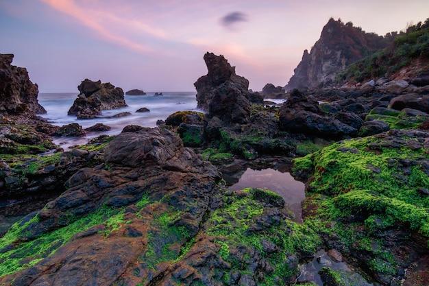 Avondrood, rots en beweging van het strand. steen. koraalrif. kliffen. natuur. zee landschap. wolk. landschapsfoto. pantai watulumbung, gunungkidul yogyakarta.