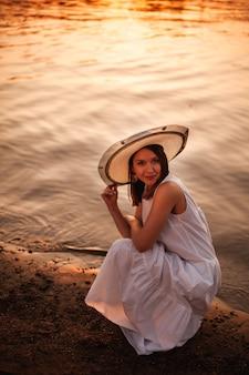 Avondwandeling langs de rivier bij een vurige oranje zonsondergang een vrouw in een jurk en een hoed zit aan de rand...