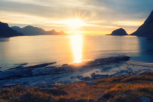 Avondzonsondergang op strand haukland met wit zand, en bergen de lofoten-eilanden in polair noorwegen