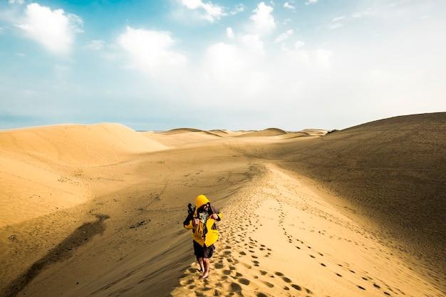 Avonturier eenzame wandelaar in zandwoestijn met oneindig - zanderige duinen overal voor alternatieve wilde vakantie voor mensen houden van gelukkige levensstijl in buitenruimtes - vreugde van reizen concept