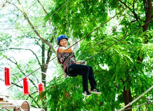 Avontuur dat hoog draadpark beklimt - vrouw op koers in berghelm en veiligheidsuitrusting